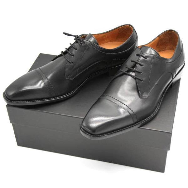 Foto Italienische Herrenschuhe schwarz mit Zehenkappe und markanter Sohle auf schwarzem Schuhkarton_Modell 112