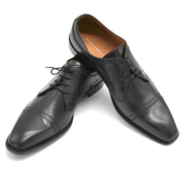 Foto Italienische Herrenschuhe schwarz mit Zehenkappe und markanter Sohle beide mit der Spitze nach vorn weisend. Einer auf dem anderen stehend_Modell 112