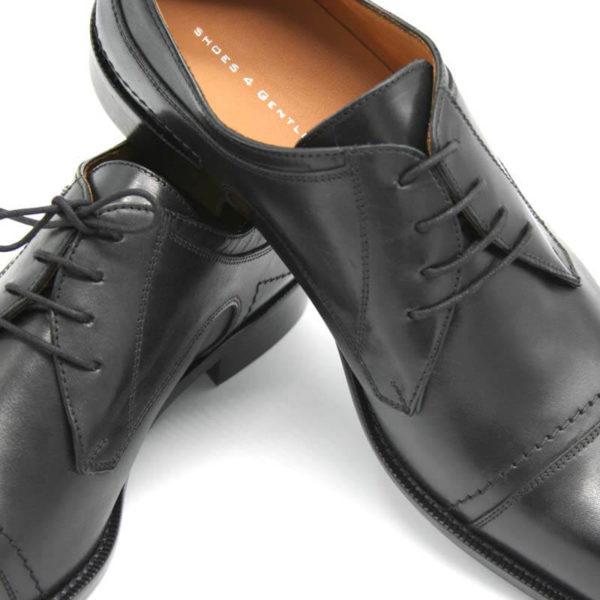 Foto Italienische Herrenschuhe schwarz mit Zehenkappe und markanter Sohle beide mit der Spitze nach links zeigend. Einer liegend, so dass die schwarze Ledersohle sichtbar ist, der andere stehend_Modell 112