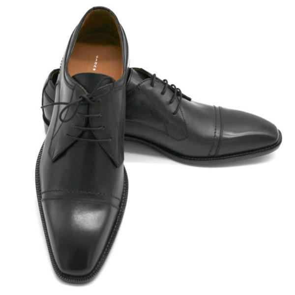 Foto Italienische Herrenschuhe schwarz mit Zehenkappe und markanter Sohle. Der rechte Schuh zeigt nach vorn und ist auf dem Linken abgestützt, der nach rechts zeigt_Modell 112