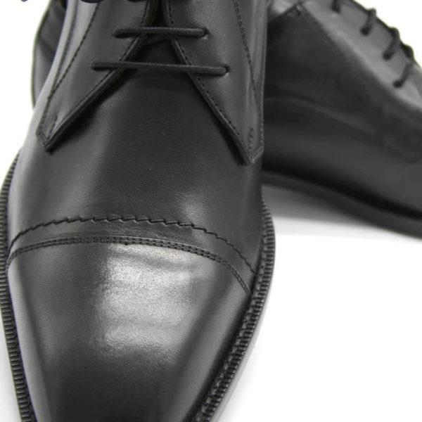 Foto Nahaufnahme Italienische Herrenschuhe schwarz mit Zehenkappe und markanter Sohle. Der rechte Schuh zeigt nach vorn und ist auf dem Linken abgestützt, der nach rechts zeigt_Modell 112