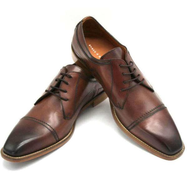 Foto Individuell und maskulin Herrenschuh Business Derby in Cognac. 2 Schuhe nach vorne zeigend; einer auf den anderen abgestützt.