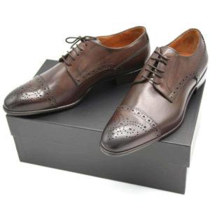 Foto Half Brogue Herrenschuh in Dunkelbraun mit Lochverzierung an der Zehenkappe auf schwarzem Schuhkarton_Modell 135