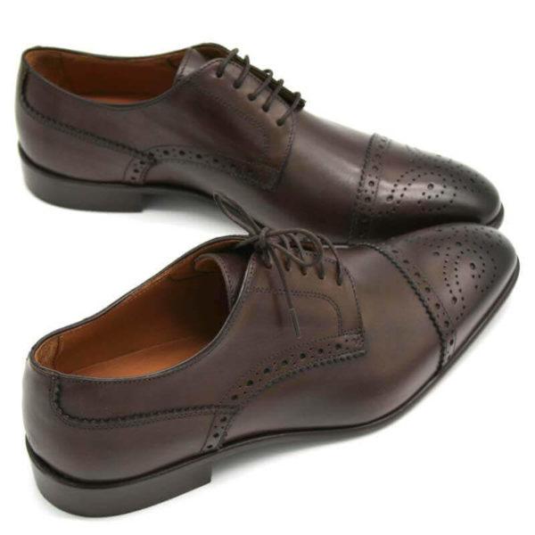 Foto Half Brogue Herrenschuh in Dunkelbraun mit Lochverzierung an der Zehenkappe. Zwei Schuhe beide nach rechts zeigend und an den Spitzen zusammen_Modell 135