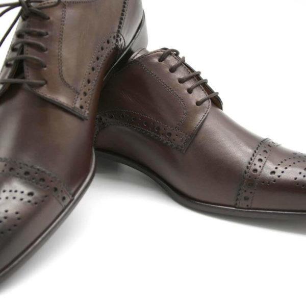 Foto Half Brogue Herrenschuh in Dunkelbraun mit Lochverzierung an der Zehenkappe. Zwei Schuhe. Der eine auf den anderen gelehnt. Nahaufnahme_Modell 135