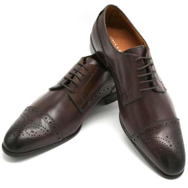 Foto Half Brogue Herrenschuh in Dunkelbraun mit Lochverzierung an der Zehenkappe. Zwei Schuhe beide nach links zeigend, einer liegend, so dass die Ledersohle zu sehen ist_Modell 135