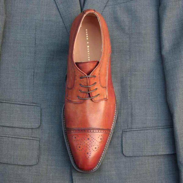 Foto von einem Business Schuh in braun mit Captoe Verziehrung Ausschnitt zeigt den Schuh auf einer Anzugjacke - Modell 232 Topmodischer Allrounder