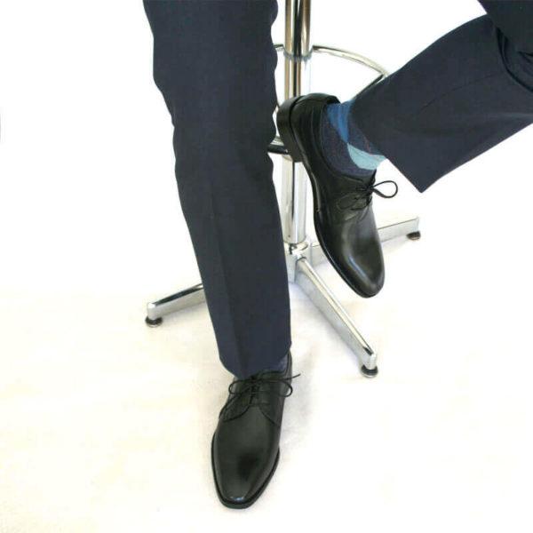 Foto von zwei schwarzen Derby Glattleder Herrenschuhen an den Füßen eines Herren, der auf einem Barhocker sitzt. Es sind nur die Hosenbeine, die Socken und der untere Teil des Barhockers und die Schuhe zu sehen. Ein Schuh ist auf dem Boden aufgestellt, der andere auf die Fußstütze des Barhockers gestellt . Modell Stil Statement