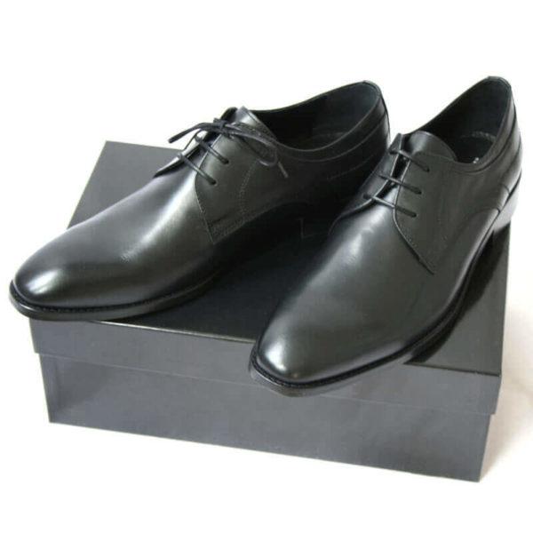 Foto von zwei schwarzen Derby Glattleder Herrenschuhen auf schwarzem Schuhkarton. Modell Stil Statement
