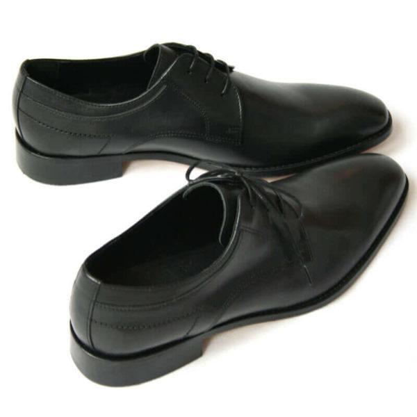 Foto von zwei schwarzen Derby Glattleder Herrenschuhen. Beide nach rechts zeigend. Einer quer stehend. Die Schuhspitzen berühren sich. Modell Stil Statement