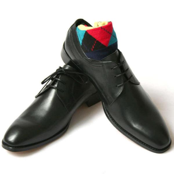 Foto von zwei schwarzen Derby Glattleder Herrenschuhen. Der rechte Schuh steht auf dem anderen und ein buntes Sockenpaar schaut heraus. Modell Stil Statement