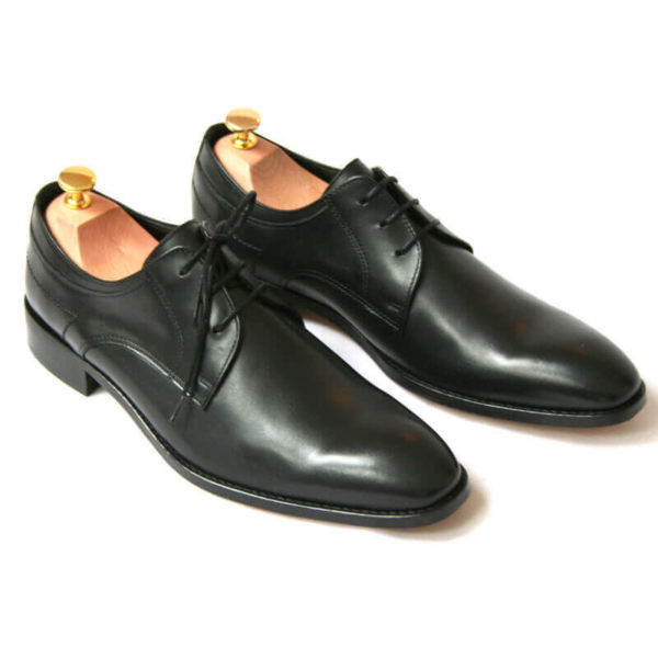 Foto von zwei schwarzen Derby Glattleder Herrenschuhen. Beide zeigen nach rechts unten und sind mit Schuhspannern mit Goldknöpfen versehen. Modell Stil Statement