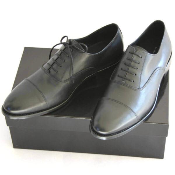 Foto von zwei schwarzen Oxford Glattleder Herrenschuhen mit Zehenkappe auf schwarzem Schuhkarton. Modell Oxford Pro