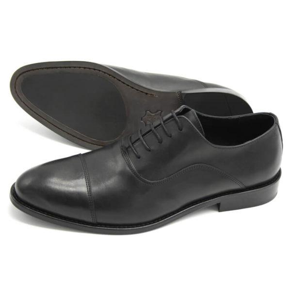 Foto von zwei schwarzen Oxford Pro Glattleder Herrenschuhen mit Zehenkappe. Einer liegend, so das die genähte Sohle mit Gummikeil zu sehen ist. Der andere schräg nach links vorne zeigend . Modell Oxford Pro
