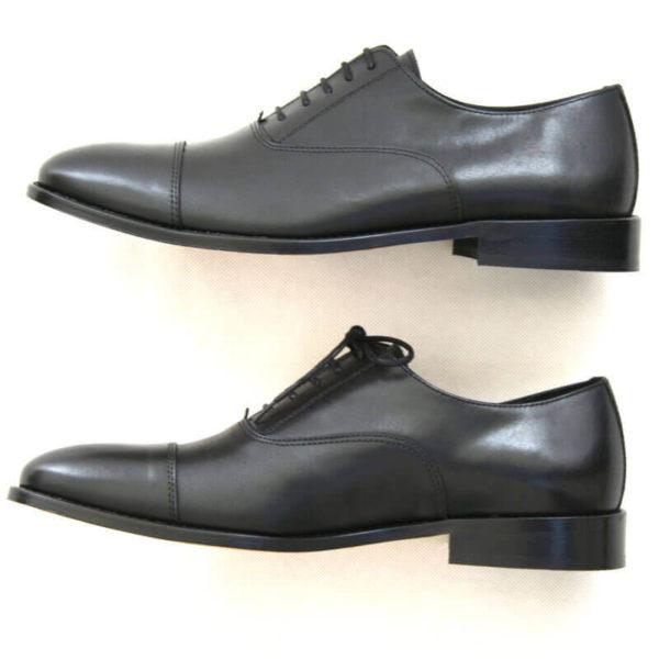 Foto von zwei schwarzen Oxford Glattleder Herrenschuhen mit Zehenkappe. Beide von der Seite nach links zeigend. Modell Oxford Pro