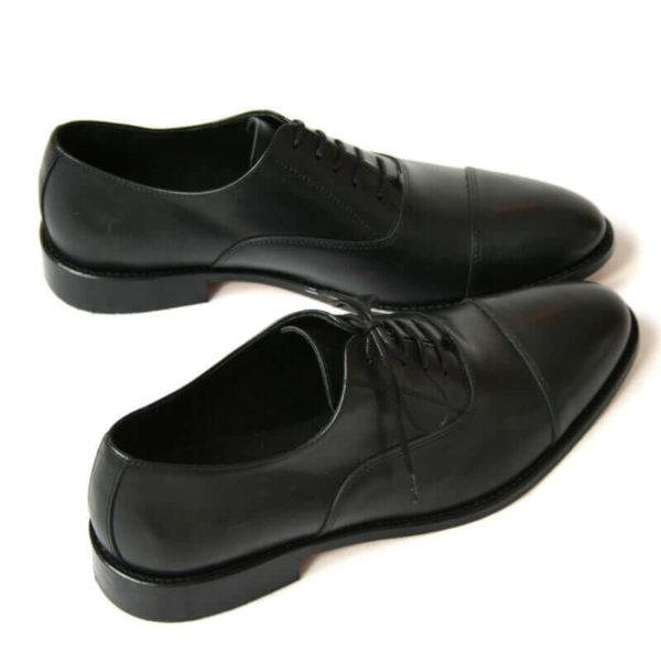 Foto von zwei schwarzen Oxford Glattleder Herrenschuhen mit Zehenkappe. Beide nach rechts zeigend. Einer quer stehend. Die Schuhspitzen berühren sich. Modell Oxford Pro
