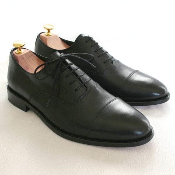 Foto von zwei schwarzen Oxford Glattleder Herrenschuhen mit Zehenkappe. Beide zeigen nach rechts unten und sind mit Schuhspannern mit Goldknöpfen versehen. Modell Oxford Pro
