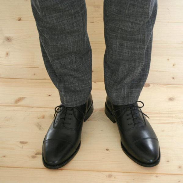 Foto von Herrenbeinen im grauen Anzug mit zwei schwarzen Oxford Glattleder Herrenschuhen mit Zehenkappe. Modell Oxford Pro