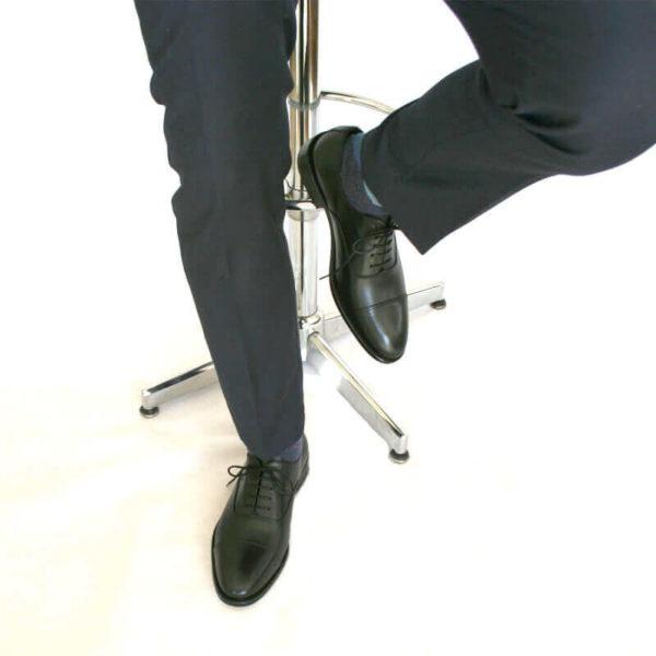 Foto von zwei schwarzen Oxford Glattleder Herrenschuhen mit Zehenkappe an den Füßen eines Herren, der auf einem Barhocker sitzt. Es sind nur die Hosenbeine, die Socken und der untere Teil des Barhockers und die Schuhe zu sehen. Ein Schuh ist auf dem Boden aufgestellt, der andere auf die Fußstütze des Barhockers gestellt . Modell Oxford Pro