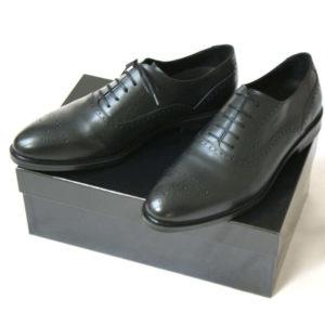 Foto von zwei schwarzen Oxford Glattleder Herrenschuhen mit Verzierung auf schwarzem Schuhkarton. Modell Oxford Plus