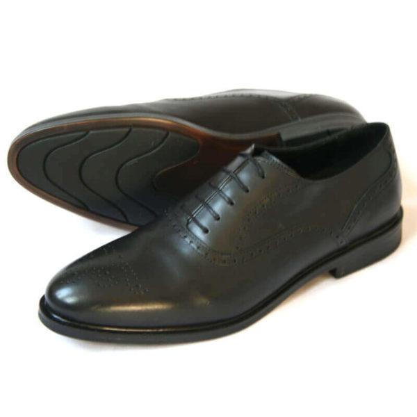 Foto von zwei schwarzen Oxford Glattleder Herrenschuhen mit Verzierung. Einer liegend, so das die rutschfeste Sohle zu sehen ist. Der andere schräg nach links vorne zeigend . Modell Oxford Plus