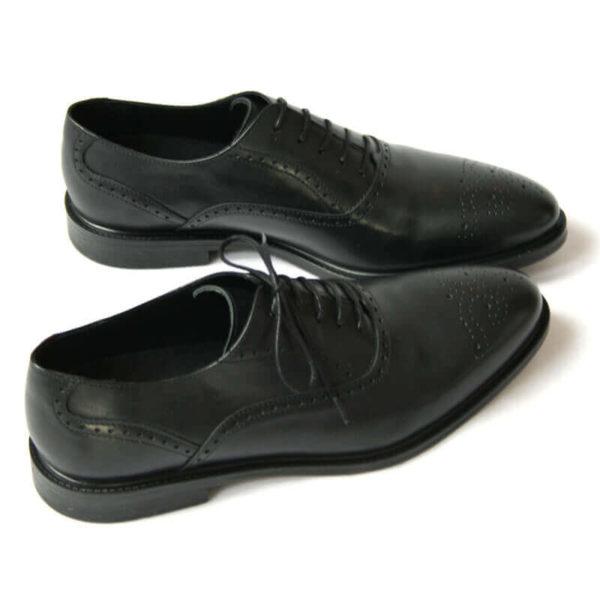 Foto von zwei schwarzen Oxford Glattleder Herrenschuhen mit Verzierung. Beide nach rechts zeigend. Einer quer stehend. Die Schuhspitzen berühren sich. Modell Oxford Plus