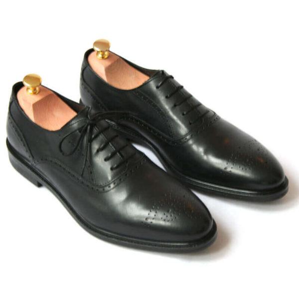 Foto von zwei schwarzen Oxford Glattleder Herrenschuhen mit Verzierung. Beide zeigen nach rechts unten und sind mit Schuhspannern mit Goldknöpfen versehen. Modell Oxford Plus