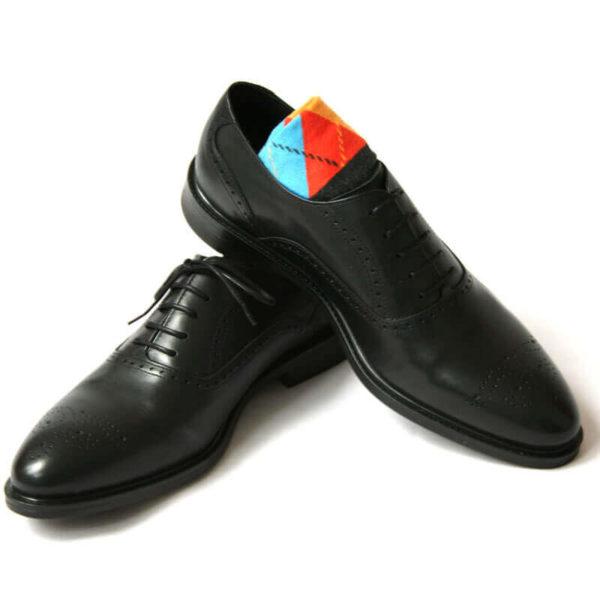 Foto von zwei schwarzen Oxford Glattleder Herrenschuhen mit Verrzierung. Der rechte Schuh steht auf dem anderen und ein buntes Sockenpaar schaut heraus. Modell Oxford Plus