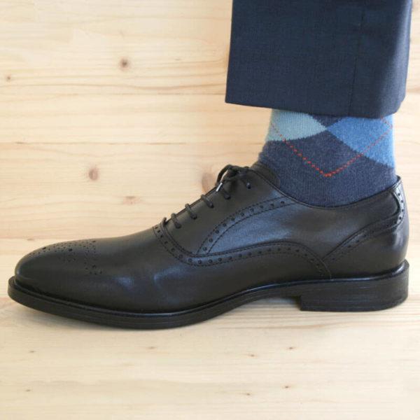 Foto von einem schwarzen Oxford Glattleder Herrenschuh mit Verzierung. Seitliche Ansicht. Nach links weisend. Der untere Teil einer dunkelblauen Anzughose und Strumpf sind zu sehen. Modell Oxford Plus