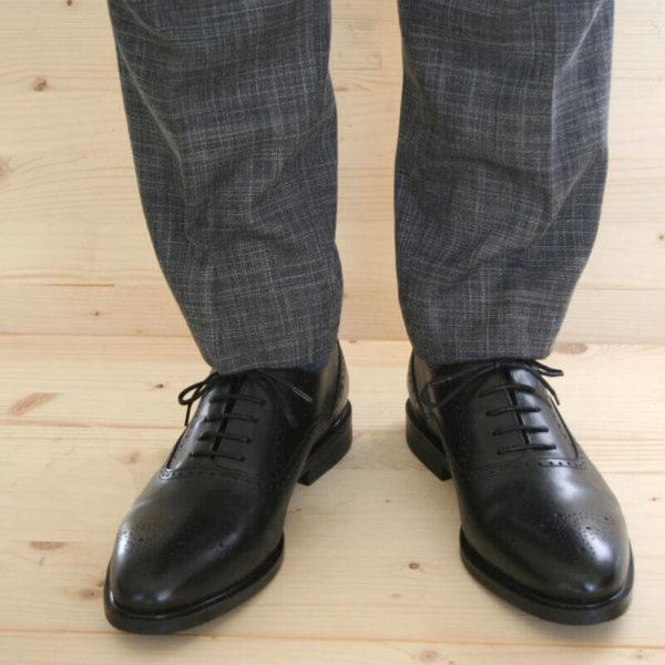 Foto von Herrenbeinen im grauen Anzug mit zwei schwarzen Oxford Glattleder Herrenschuhen mit Verzierung. Modell Oxford Plus