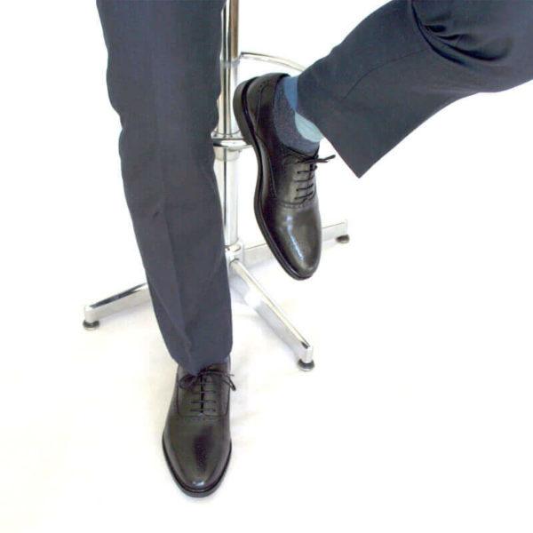 Foto von zwei schwarzen Oxford Glattleder Herrenschuhen mit Verzierung. An den Füßen eines Herren, der auf einem Barhocker sitzt. Es sind nur die Hosenbeine, die Socken und der untere Teil des Barhockers und die Schuhe zu sehen. Ein Schuh ist auf dem Boden aufgestellt, der andere auf die Fußstütze des Barhockers. Modell Oxford Plus