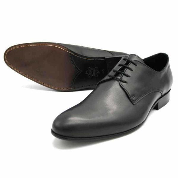 Foto von zwei schwarzen Herrenschuhen einer auf der Seite liegend, so dass die durchgenähte Sohle zu sehen ist - Modell Alltagsfavorit 304