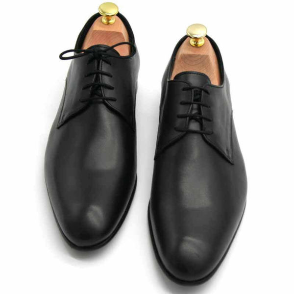 Foto von zwei schwarzen Herrenschuhen beide mit Schuhspannern mit goldenem Knauf, nach vorne weisend - Modell Alltagsfavorit 304
