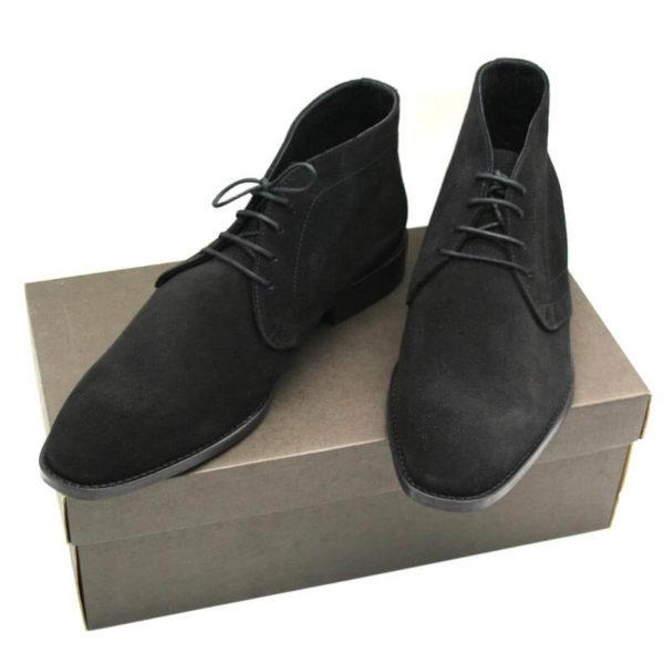 Foto_Wildleder Stiefelette Herren_zwei Herrenstiefeletten in schwarzem Rauleder beide auf braunem Schuhkarton nach vorne weisend. Modell 307