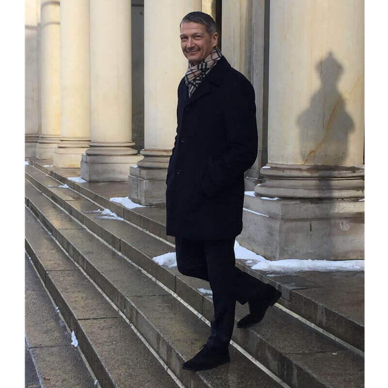 Foto mit gut gekleidetem Mann in Mantel und Schal, der die Treppen eines Gebäudes mit Säulen runter geht. An den Füßen trägt er Herren Oxford Schuhe in schwarzem Wildleder.