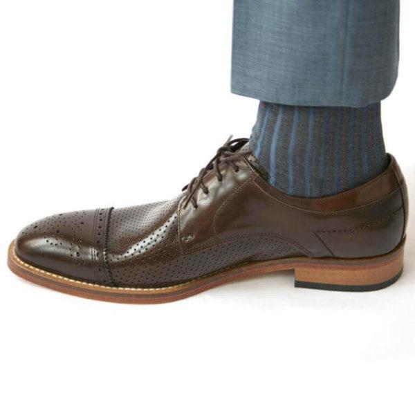 Foto-Ein brauner Herrenschuh mit Teilperforation und gemusterter Zehenkappe nach links zeigend mit Socke und hellblauem Anzughosenbein. Modell Komfortabler Trendsetter-5