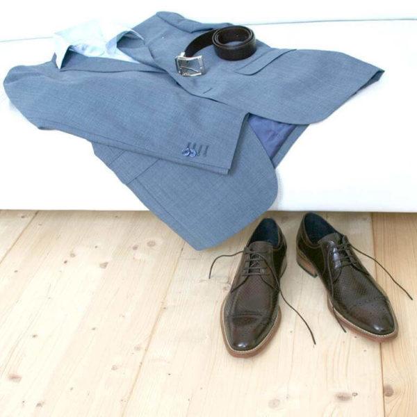 Foto-2 braune Herrenschuhe mit Teilperforation und gemusterter Zehenkappe vor weißer Couch auf der hellblauer Anzug mit Hemd und Gürtel liegt. Modell Komfortabler Trendsetter-8