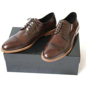 Foto-Zwei braune Herrenschuhe mit Teilperforation und schlichter Zehenkappe auf schwarzem Schuhkarton-1