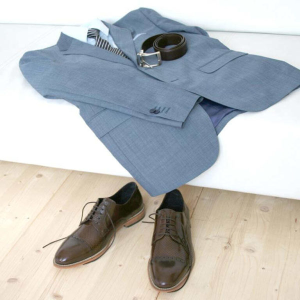Foto-2 braune Herrenschuhe mit Teilperforation vor weißer Couch mit hellblauem Anzug mit Hemd und Gürtel. Modell: Komfortabler Klassiker-8