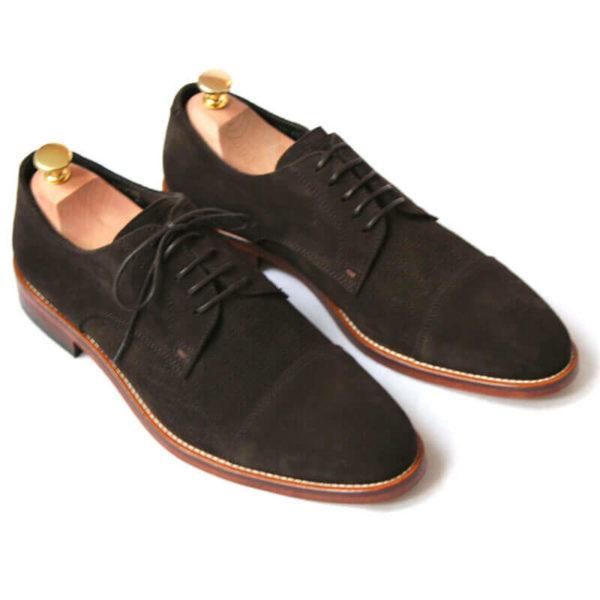 Foto von zwei mokkafarbenen Derby Rauleder Herrenschuhen mit Zehenkappe. Beide zeigen nach rechts unten und sind mit Schuhspannern mit Goldknöpfen versehen. Modell Top Wildleder