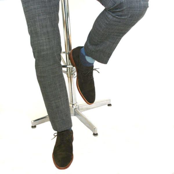 Foto von zwei mokkafarbenen Derby Rauleder Herrenschuhen mit Zehenkappe an den Füßen eines Herren, der auf einem Barhocker sitzt. Es sind nur die Hosenbeine, die Socken und der untere Teil des Barhockers und die Schuhe zu sehen. Ein Schuh ist auf dem Boden aufgestellt, der andere auf die Fußstütze des Barhockers. Modell Top Wildleder