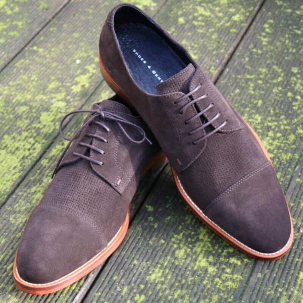 Foto von zwei mokkafarbenen Derby Rauleder Herrenschuhen mit Zehenkappe. Der rechte Schuh steht auf dem anderen. Modell Top Wildleder