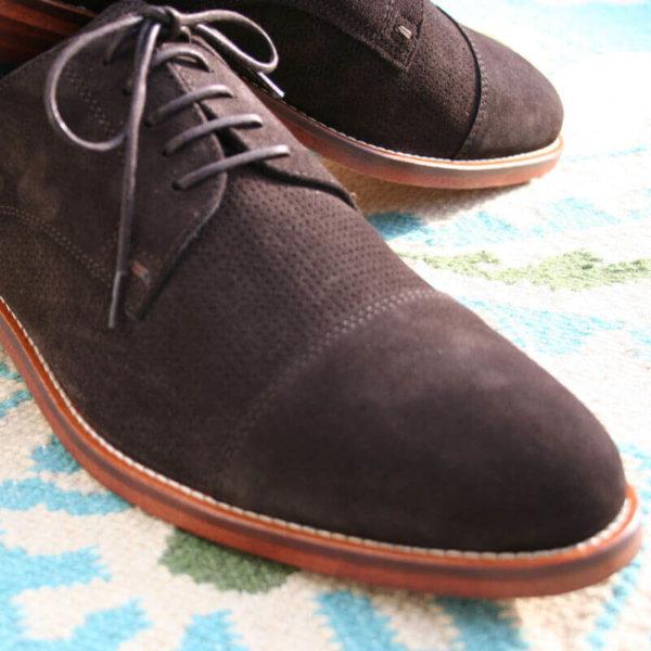 Foto von zwei mokkafarbenen Derby Rauleder Herrenschuhen mit Zehenkappe. Nahaufnahme, so dass nur der vordere Teil der Schuhe zu sehen ist. Auf Teppich. Modell Top Wildleder