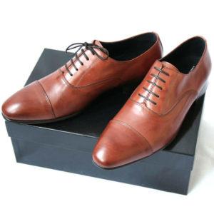 Foto von zwei braunen Oxford Glattleder Herrenschuhen mit Zehenkappe auf schwarzem Schuhkarton. Modell Oxford first