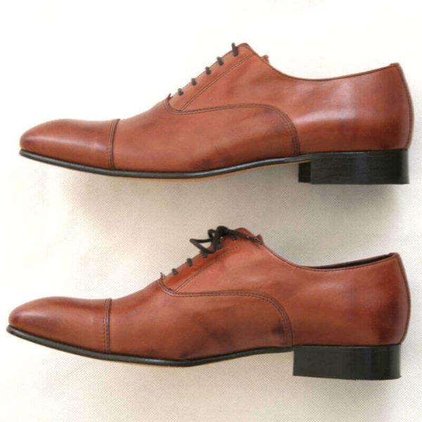 Foto von zwei braunen Oxford Glattleder Herrenschuhen mit Zehenkappe. Beide von der Seite nach links zeigend. Modell Oxford first