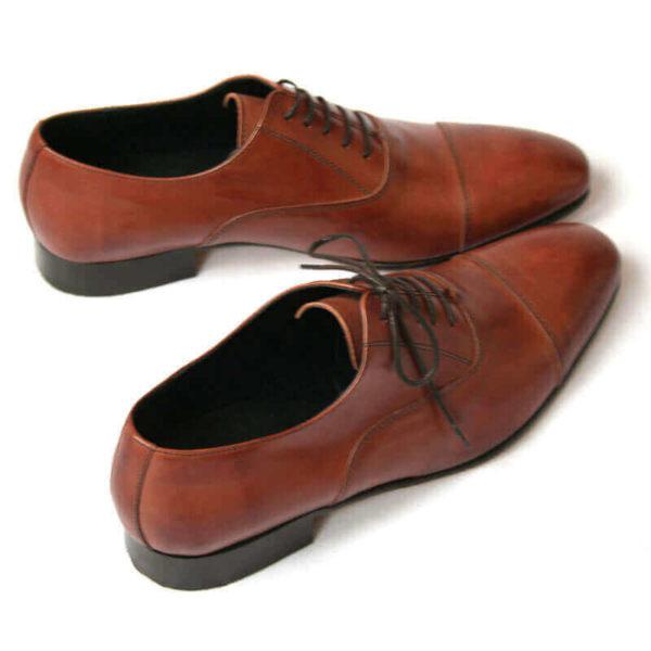 Foto von zwei braunen Oxford Glattleder Herrenschuhen mit Zehenkappe. Beide nach rechts zeigend. Einer quer stehend. Die Schuhspitzen berühren sich. Modell Oxford first