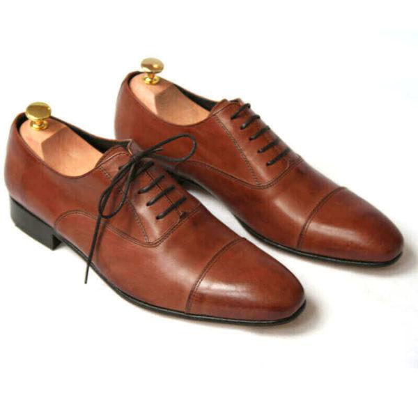 Foto von zwei braunen Oxford Glattleder Herrenschuhen mit Zehenkappe. Beide zeigen nach rechts unten und sind mit Schuhspannern mit Goldknöpfen versehen. Modell Oxford first