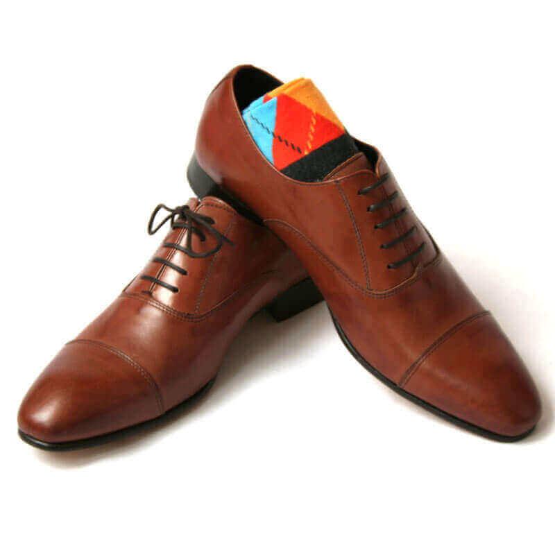 Foto von zwei braunen Oxford Glattleder Herrenschuhen mit Zehenkappe. Der rechte Schuh steht auf dem anderen und ein buntes Sockenpaar schaut heraus. Modell Oxford first