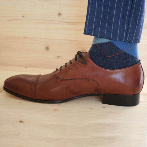 Foto von einem braunen Oxford Glattleder Herrenschuh mit Zehenkappe. Seitliche Ansicht. Nach links weisend. Der untere Teil einer dunkelblauen Anzughose und Strumpf sind zu sehen. Modell Oxford first