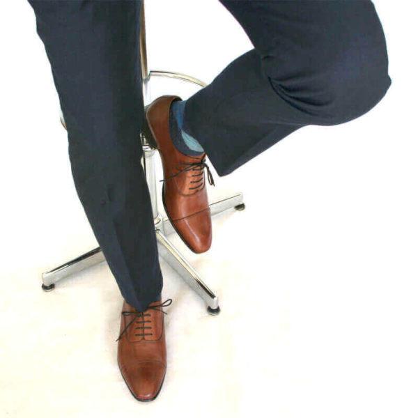 Foto von zwei braunen Oxford Glattleder Herrenschuhen mit Zehenkappe an den Füßen eines Herren, der auf einem Barhocker sitzt. Es sind nur die Hosenbeine, die Socken und der untere Teil des Barhockers und die Schuhe zu sehen. Ein Schuh ist auf dem Boden aufgestellt, der andere auf die Fußstütze des Barhockers gestellt. Modell Oxford first